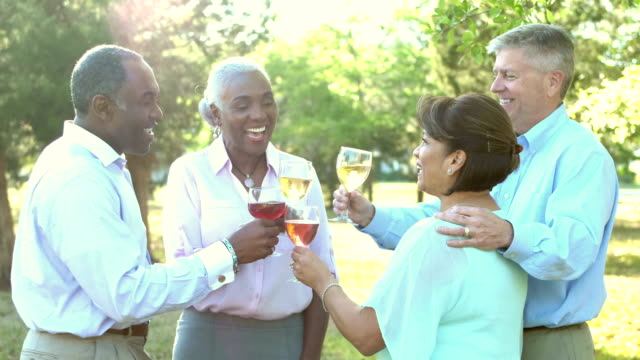 two multi-ethnic couples talking, drinking wine outdoors - 50 59 years stock videos & royalty-free footage