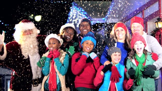zwei multi-ethnische familien beim winterfest mit dem weihnachtsmann - joy stock-videos und b-roll-filmmaterial