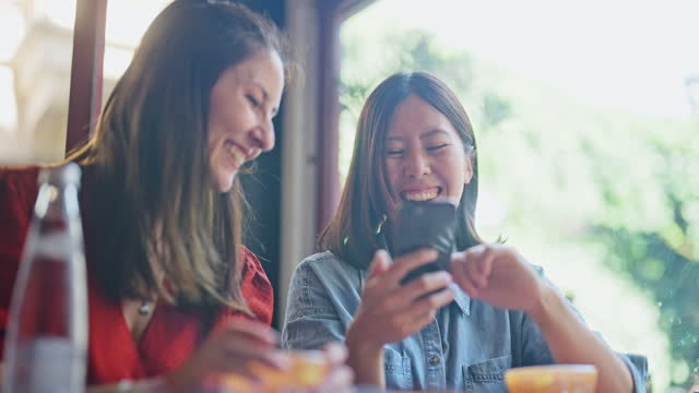 two multi-ethnic female friends enjoying their time in cafe and using smart phone together - city break stock videos & royalty-free footage