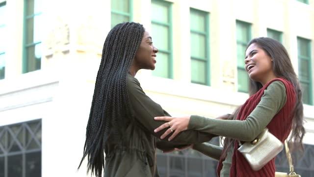 vidéos et rushes de deux copines multiethniques se réunissant - les bras écartés