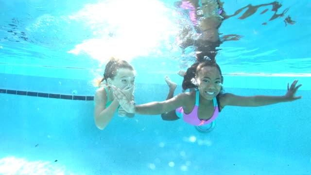 two multi-ethnic girls swimming underwater in pool - swimwear stock videos & royalty-free footage