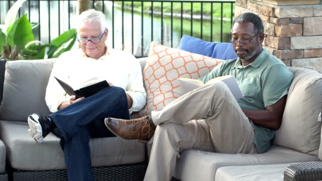 two multi-ethnic men on patio reading books - cross legged stock videos & royalty-free footage