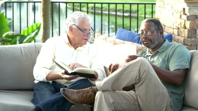 stockvideo's en b-roll-footage met twee multi-etnische mannen op patio lezen boeken - debat