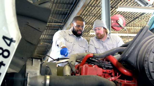 vidéos et rushes de deux hommes multiethniques travaillant sur le moteur de semi-camion - technicien de maintenance