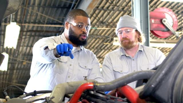 zwei multiethnische männer arbeiten auf sattelzug - motor stock-videos und b-roll-filmmaterial