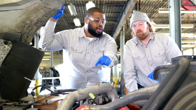 vidéos et rushes de deux hommes multiethniques travaillant sur le moteur de semi-camion - mécanicien