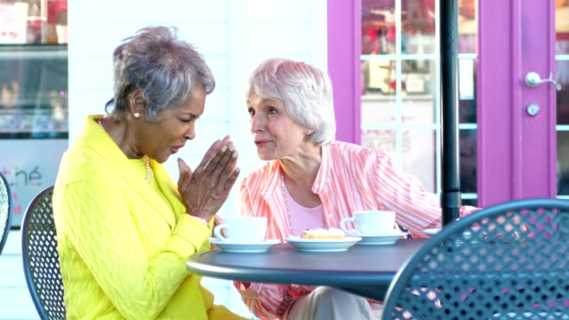 Two multi-ethnic senior women chatting over coffee