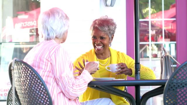 stockvideo's en b-roll-footage met twee multi-etnische senior vrouwen chatten over koffie - 70 79 jaar