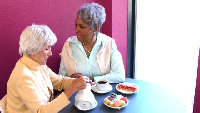 stockvideo's en b-roll-footage met twee multi-etnische senior vrouwen gesprek in een koffiehuis - 70 79 jaar