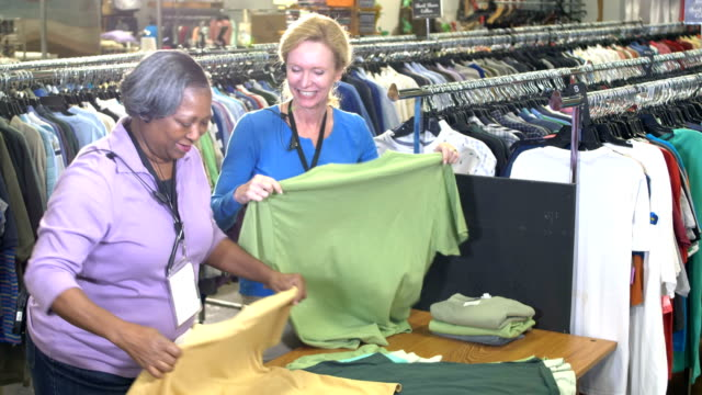 two multi-ethnic women working in clothing store talking - retail manager stock videos & royalty-free footage