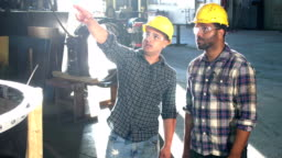 Two multi-ethnic workers in metal fabrication shop