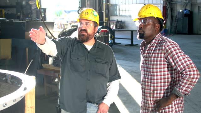 vídeos de stock e filmes b-roll de two multi-ethnic workers in metal fabrication shop - 40 44 anos