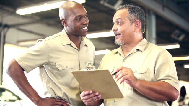 two multi-ethnic workers in warehouse, with checklist - etnia latino americana video stock e b–roll