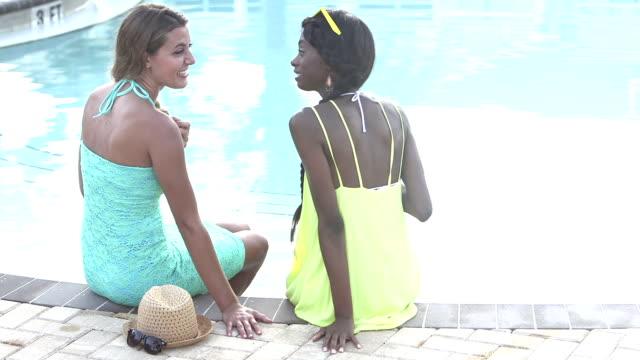 vidéos et rushes de deux jeunes femmes multiethniques parlent près de la piscine - petite amie