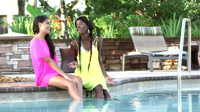 Two multi-ethnic young women talk poolside