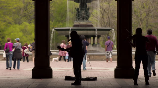 two musicians play in central park by the fountain.  people walk by. - colonna architettonica video stock e b–roll