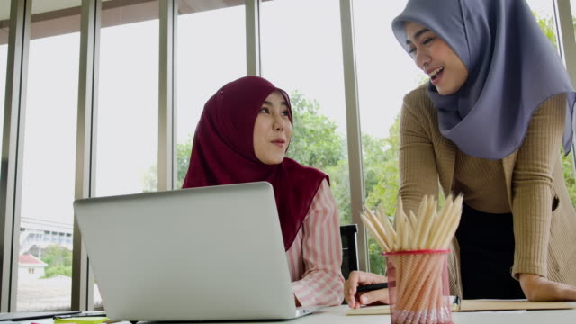 two muslim business woman in traditional hijab clothing working and discussing  in modern office.new normal concept. - hijab stock videos & royalty-free footage