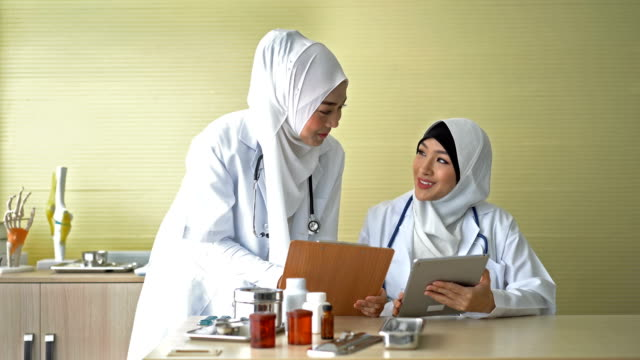 4k two muslim female doctors discussion in doctor's office - medical occupation stock videos & royalty-free footage