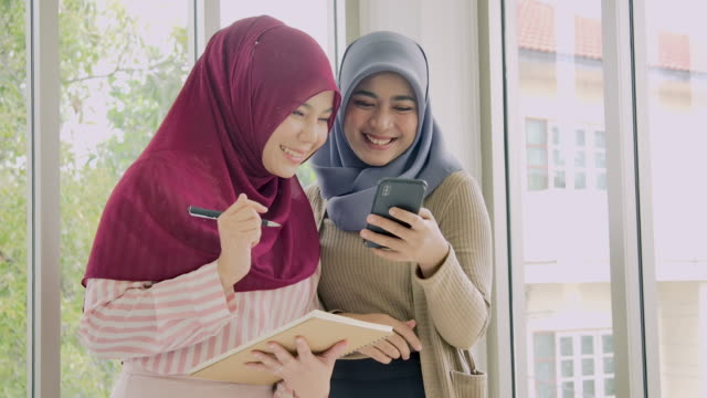 two muslim friends using and looking mobile phone. - gossip stock videos & royalty-free footage