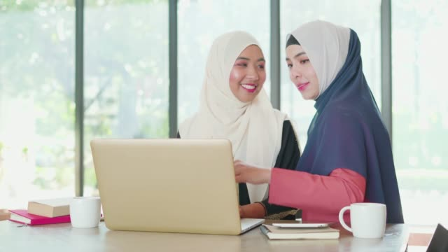 two muslim people working and discussion with laptop at working space. - kufi stock videos & royalty-free footage