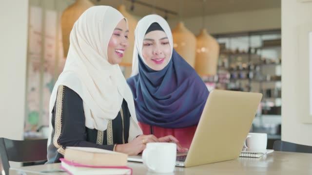 vidéos et rushes de deux personnes musulmanes travaillant et discutant avec l'ordinateur portatif à l'espace de travail. - moyen orient