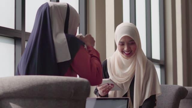 vidéos et rushes de deux personnes musulmanes travaillant et discutant avec la tablette et l'ordinateur portatif dans le café-magasin. - moyen orient