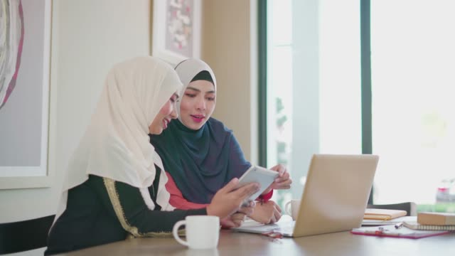 two muslim people working and discussion with tablet and laptop in coffee shop. - kufi stock videos & royalty-free footage