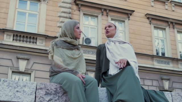 vídeos de stock, filmes e b-roll de duas mulher muçulmana ter uma conversa - vestuário modesto