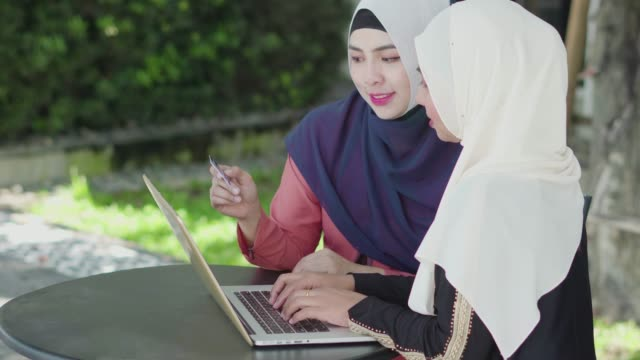 two muslim women shopping online with credit card and laptop. - religious dress stock videos & royalty-free footage