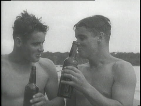 two naked men sit on the beach drinking beer - homosexual stock videos & royalty-free footage