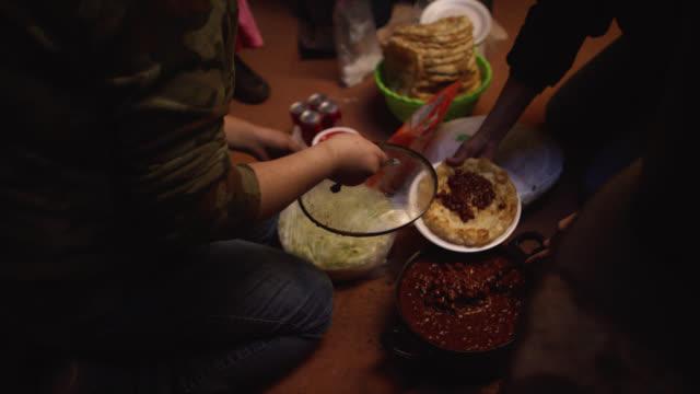 två native american (navajo) kvinnor i fyrtioårsåldern scoop bönor på tortillas (fry bröd) som de förbereder mat för resten av sin familj inomhus - nordamerikansk indiankultur bildbanksvideor och videomaterial från bakom kulisserna