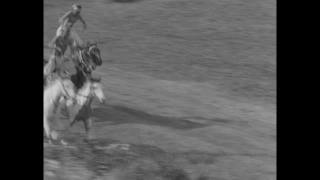 two native american women riding around ring / two native american men standing riding two horses each / native american men riding bucking broncos /... - bucking stock videos & royalty-free footage