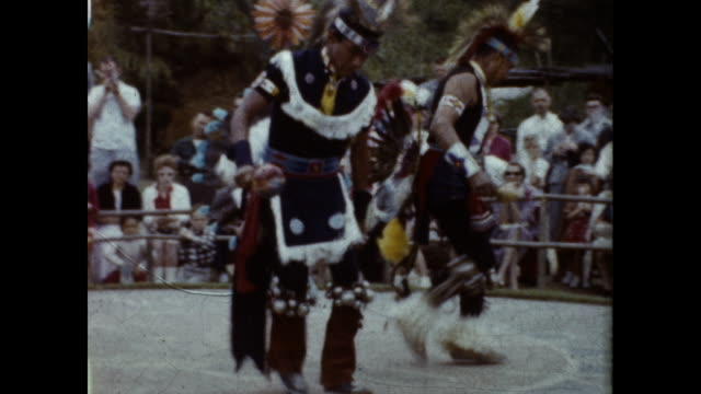 two native americans performing a dance in a circle for big crowd of people surrounding the circle - native american ethnicity stock videos & royalty-free footage