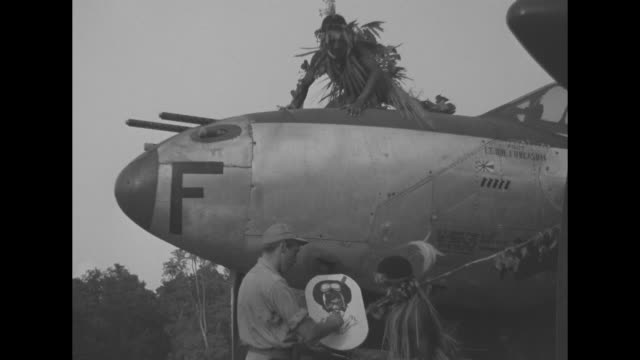 two native guineans carrying tree branches approach a lockheed p38 with the pilot perched on top / the pilot flaps his arms pantomiming flying / a... - newsreel stock videos & royalty-free footage