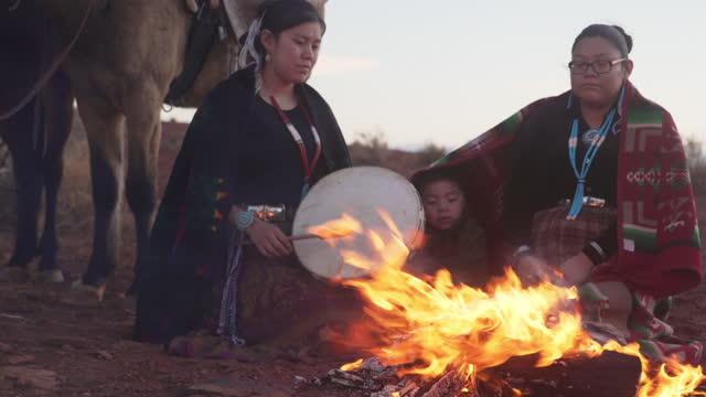 vídeos y material grabado en eventos de stock de dos hermanas navajo con su hermanito alrededor de un incendio en monument valley - arizona - western usa
