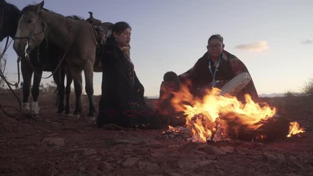 vídeos de stock, filmes e b-roll de duas mulheres navajo e um garotinho em torno de uma fogueira com cavalos em monument valley - arizona - índio americano