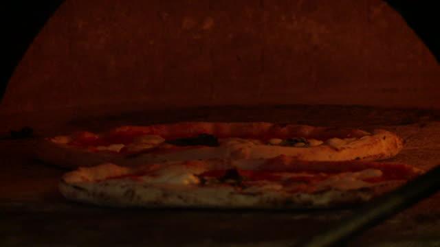 ms two neapolitan pizzas in wood oven / isernia, molise, italy  - ナポリ点の映像素材/bロール