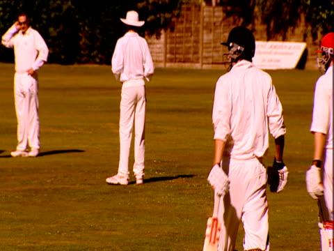 vídeos de stock e filmes b-roll de two new batsmen walk onto the field during a cricket match. - enfeites para a cabeça