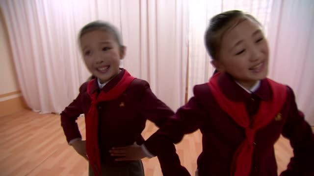 Two North Korean school children singing about being soldiers in the countries army