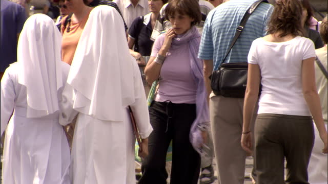 stockvideo's en b-roll-footage met two nuns walk past a crowd of tourists in vatican city. - non urban scene