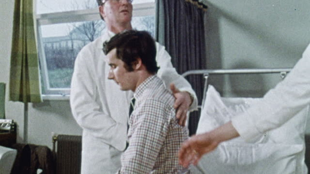 TS Two nurses carrying a patient from hospital bed to chair as other nurses look on / Plymouth, England, United Kingdom
