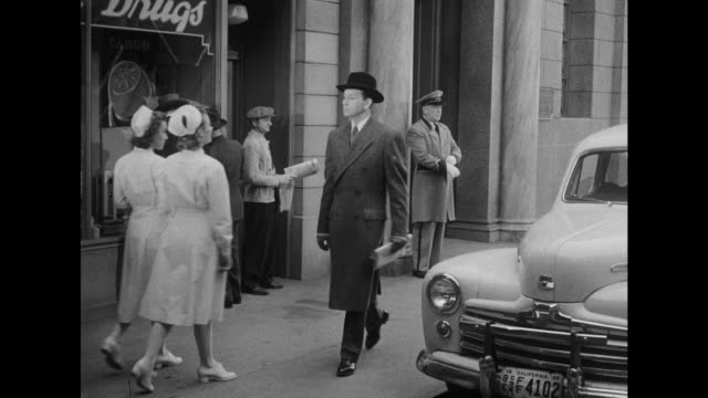 1948 two nurses greet doctor while passing on street - film noir style stock videos & royalty-free footage