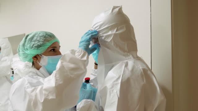 vídeos y material grabado en eventos de stock de dos enfermeras ayudándose mutuamente con equipo de protección en el pasillo del hospital - trabajador de primera línea
