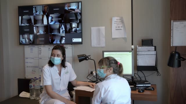 two nurses talk about a patient from a control room, with an videocontrol screen, during the coronavirus pandemic at the hotel plaza, which is... - female nurse stock videos & royalty-free footage