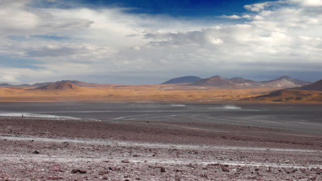 two off road cars in the distance riding over the bolivian landscape - bolivian andes stock videos & royalty-free footage