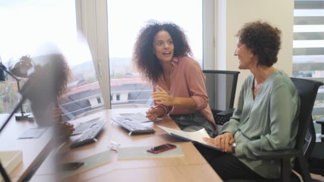 vídeos de stock e filmes b-roll de two office colleagues chatting lively. - parceria