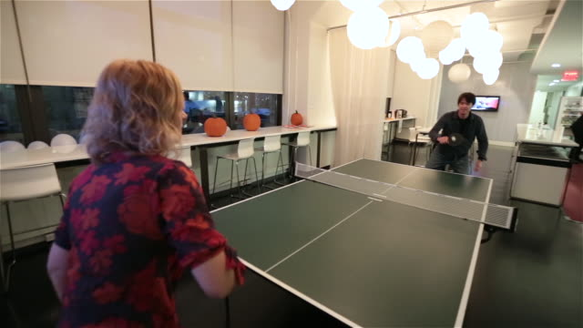 two office workers play ping-pong game in big corporate break-room - table tennis stock videos & royalty-free footage