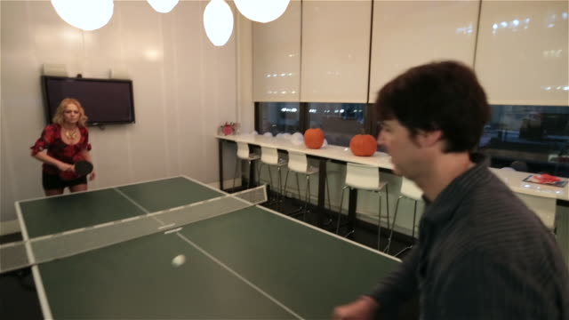 Two office workers play ping-pong game in big corporate break-room