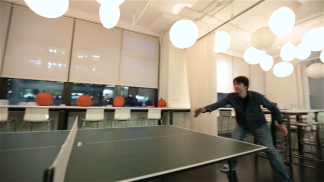 Two office workers play ping-pong game in big corporate break-room (back-and-forth)