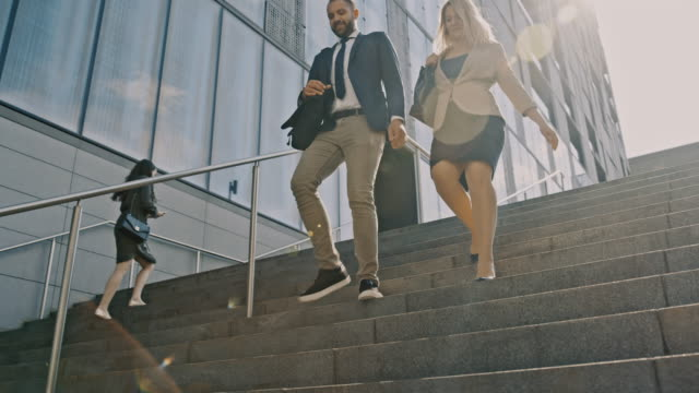 slo mo two office workers walking down stairs into an underpass - skirt stock videos & royalty-free footage
